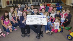 Neil Wakelin, manager of the Tamworth Co-op convenience store in Lichfield, hands over a cheque for £661 to Wade Street Church Playgroup in front of delighted group of organisers, mums and tots.