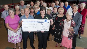 Julie-Ann Kester, manager of the Tamworth Co-op convenience store in Dordon, hands over the cheque to Andy Brown, secretary of North Warwickshire Retired Miners club. Also pictured are some of the club members who will be embarking on a day trip to Llandudno.