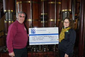 Derek Goodman, director and volunteer co-ordinator of Claymills Pumping Engines Trust, receives the cheque for £555 from Marina Hutton, manager of Tamworth Co-op Stretton store, in one of the engine rooms.