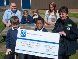 Sheila Villers, manager of Tamworth Co-op Wood End store, presents cheque for £478 to Hurley Primary School after being shown new Numicon maths aid. Head teacher Glyn Morgans is on back row.