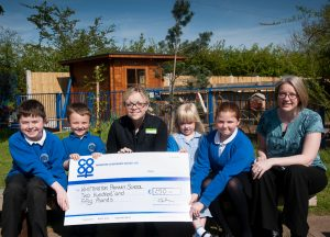 Hayley Gilbert, manager of Whittington Co-op, presenting cheque from Community Dividend Fund to Emma Taylor, deputy head of Whittington Primary School, and some pupils.