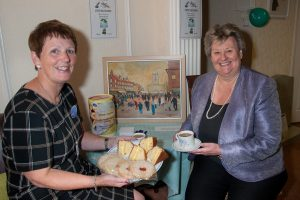 South Derbyshire MP Heather Wheeler enjoying a cuppa and a cake with bereavement and community co-ordinator Angela Bowyer.