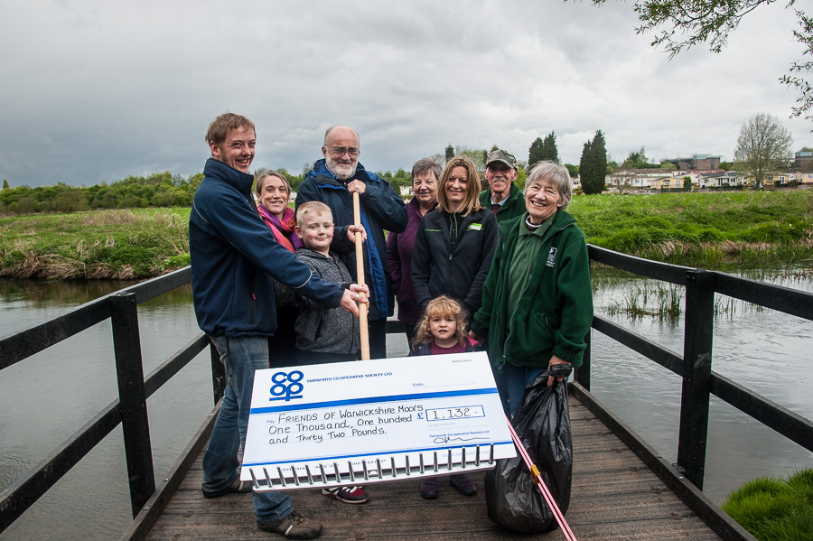 Jayne Cutforth, manager of Tamworth Co-op's Bolehall convenience store, presenting cheque to Friends of Warwickshire Moor volunteers Lee Curtis, Suzi Clark, chairman Malcolm Sanford, Lesley and Tom Barker, and secretary Pam Clark, with young helpers Oscar Hatfull (9) and Elizabeth Clark (2).