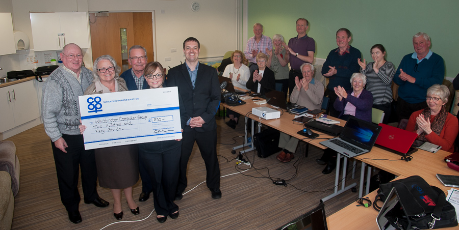 John and Wendy Gilbert are pictured receiving cheque from Hayley Gilbert, manager of Whittington Co-op. Celebrating with them are IT trainer Mark Lawrence, Cliff Jefferies and other members of Whittington Community Computer group.