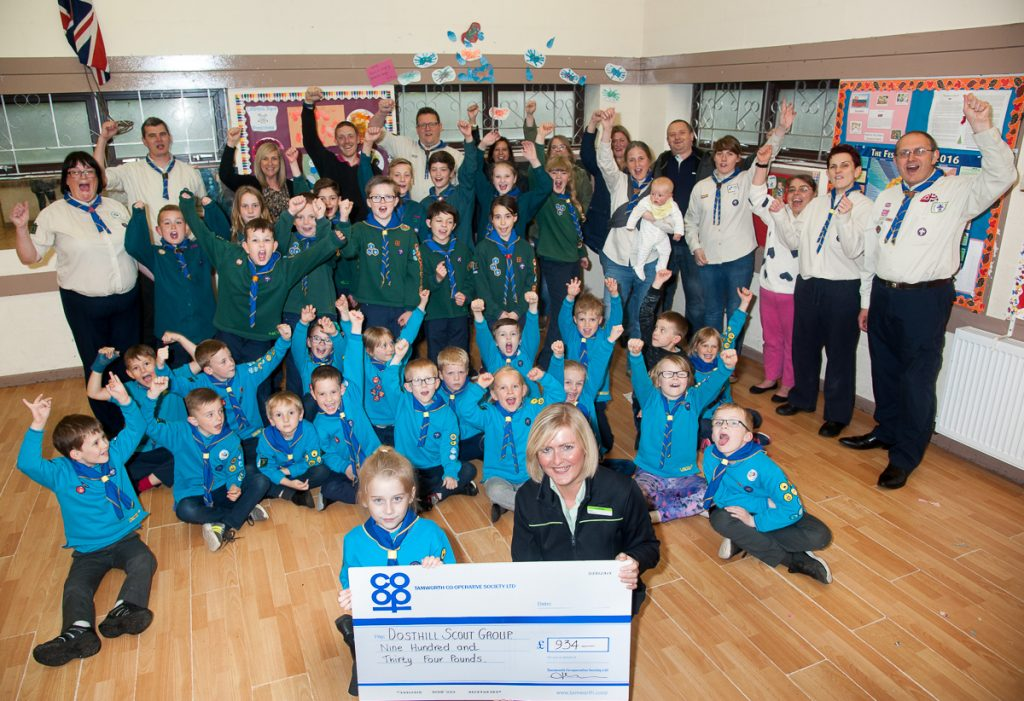 Darcii-Mai Cobden receives Community Dividend Fund cheque from Vicky Freeman, manager of Tamworth Co-op Dosthill convenience store, with Dosthill Scout Group members and leaders celebrating windfall.