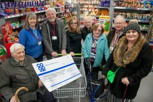 Members of Whittington and Fisherwick Good Neighbour Scheme receive Community Dividend Fund cheque at Whittington Co-op. Giant cheque is in trolley.