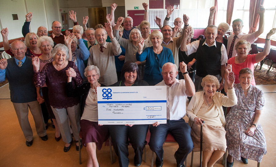 Andy Brown, secretary of North Warwickshire Retired Miners Leisure Club receives the cheque from Julie-Ann Kester, manager of Dordon Co-op, with members cheering on.