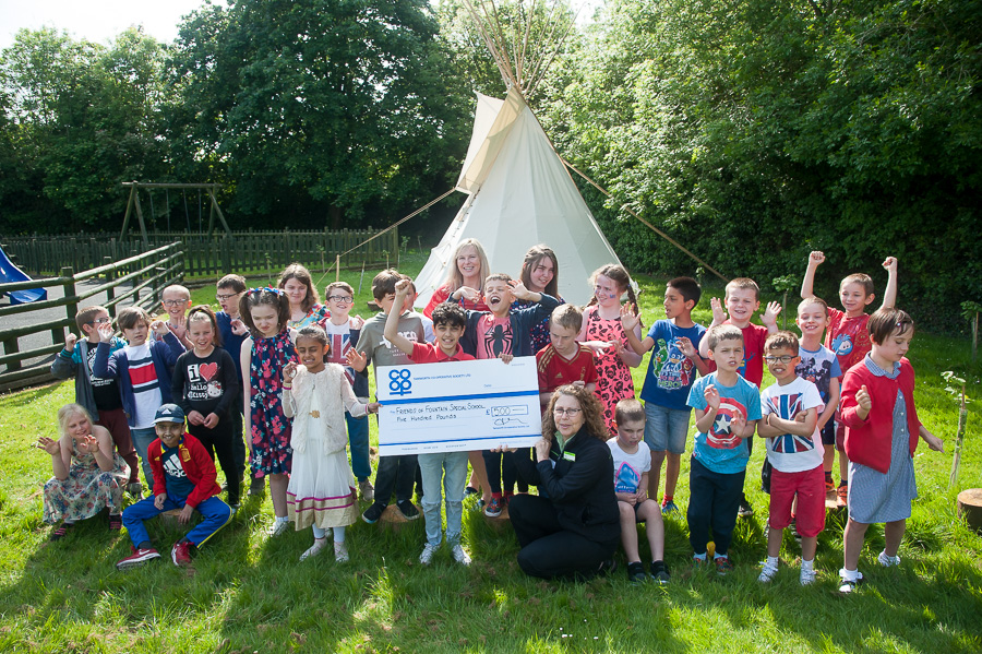 Marina Hutton, manager of Stretton Co-op, hands over Community Dividend Fund cheque to delighted pupils at Fountains Primary and head of school Nicola Price, with new tepee in background.