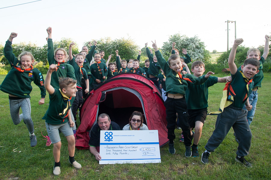 Cubs from Polesworth Abbey Scout Group jump for joy as Karl Vyse, manager of Polesworth Co-op, presents Community Dividend Fund cheque to assistant cub scout leader Shelly Keeling in front of tent.