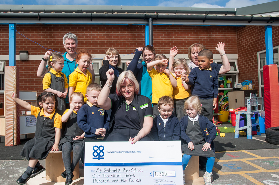 Annette Brindley, manager of Glascote Co-op, presents cheque for money raised by customers, to Theresa Miller (centre), manager of St Gabriel's Pre-school. Pictured celebrating with her are some of children who attend group and pre-school practitioners.