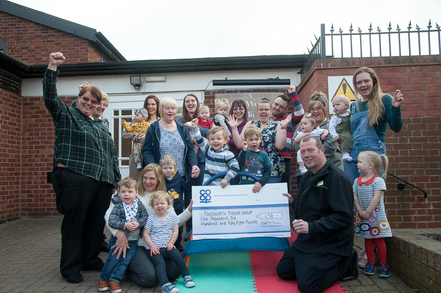 Sebastian Pirrie and Rory Broderick, who have attended Polesworth Toddler Group since babies and are leaving in September 2019, accept Community Dividend Fund cheque from Karl Vyse, manager of Polesworth Co-op. Celebrating with them are volunteers and parents from group