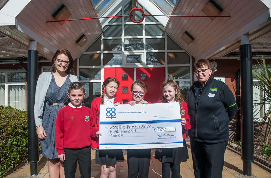 Pictured at Community Dividend Fund cheque presentation are (left) Moira Cross, head of Wood End Primary, with school's Year 6 house captains and Sheila Villers, manager of Wood End Co-op.