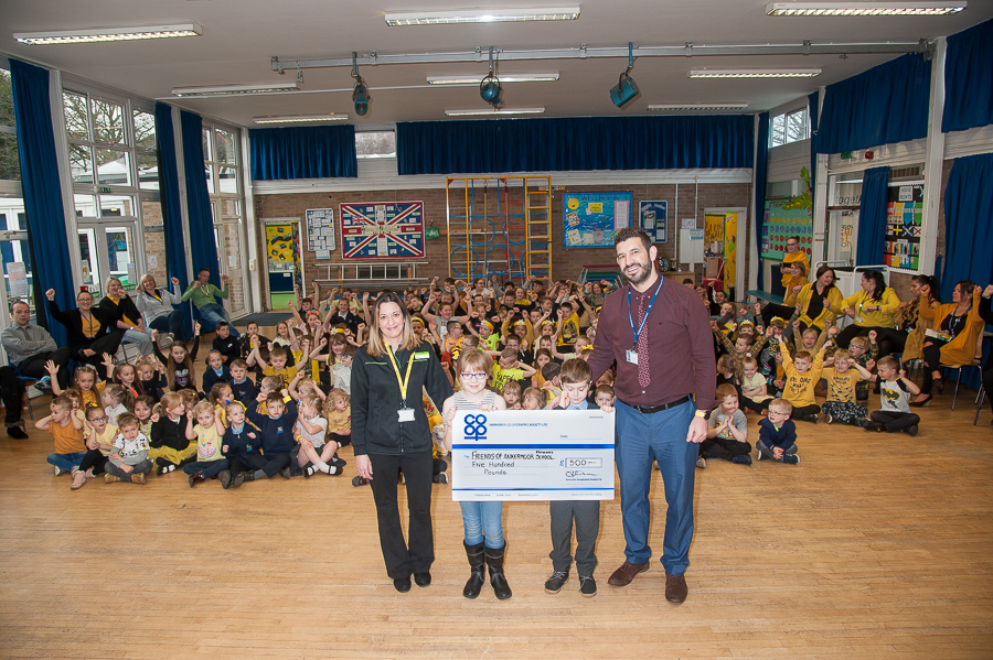 Jayne Cutforth, manager of Bolehall Co-op, presents Community Dividend Fund cheque to Simon Russell, head of Ankermoor Primary Academy, during assembly