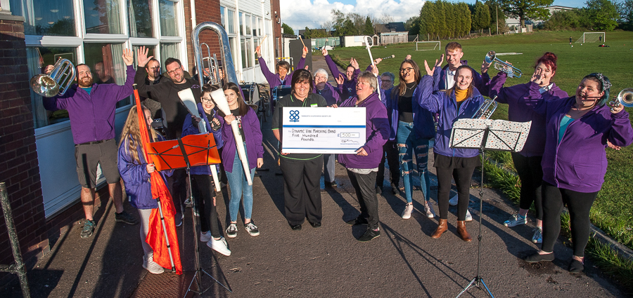 •Manager of Dordon Co-op, presents cheque to corps director of Dynamic Vibe Performance Ensemble, with jubilant members of band outside club where rehearse