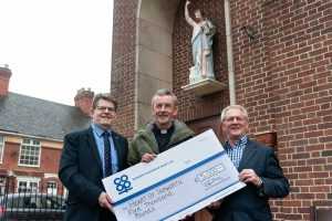 Tamworth Co-op executives hand over cheque for homeless shelter to priest