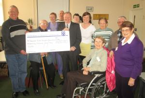 Trevor Baker, chairman and treasurer of Tamworth Stroke Patients and their Carers Group, receives a cheque from Tamworth Co-op's Ron Constable (right) in front of several members who attend the monthly meetings at the Carnegie Centre.