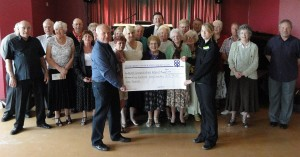 Dordon Co-op's senior supervisor Helaina Liddiard presents a cheque for £579 to Alan Brown, watched by members of North Warwickshire Retired Miners Club.