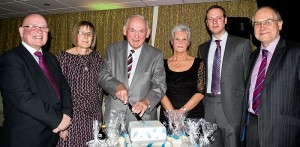 Former Tamworth Co-op chief executive Alan Glover cuts the cake celebrating the 40th anniversary of the Co-operative Employees' Long Service Association. Looking on are the four new members (from left to right) Bill Galvin, Judith Lees, Sue Williams and Dan Welsh.