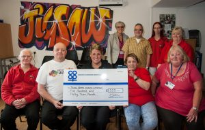 Nicky Gilbert, manager of Lichfield Co-op convenience store off Eastern Avenue, presents cheque to David Whitfield and Sue Whelan, Jigsaw events co-ordinators. Looking on are Colin Ball, chairman of North Lichfield Initiative, Staffordshire county councillor Caroline Wood and other volunteers.