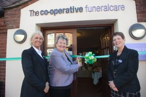 MP Heather Wheeler cuts ribbon to open coffee morning. Also pictured are funeral director Lorraine Walker and bereavement and community co-ordinator Angela Bowyer.