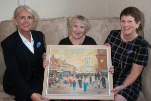 Pat Richards displays painting of Burton Market by her late husband Stan, which was auctioned to help raise funds for Macmillan cancer charity. Pictured with her are funeral director Lorraine Walker (left) and bereavement and community co-ordinator Angela Bowyer.