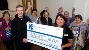 Members of Tamworth Central WI cheer as Julie Clark, manager of Tamworth Co-op supermarket, presents Community Dividend Fund cheque to Father Michael White. WI group is among organisations using new St John's Community Centre.