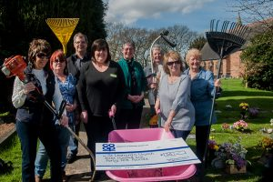 Julie-Ann Kester (fourth from left), manager of Tamworth Co-op Dordon convenience store, is pictured delivering giant cheque for money raised in wheelbarrow. Looking on are: volunteer Donna Yates, church secretary Bev Garratt, church warden Mick Dorn, Reverend Ann Simmons, church warden Sue Davis and volunteers Theresa Melia and Janet Wiggall.