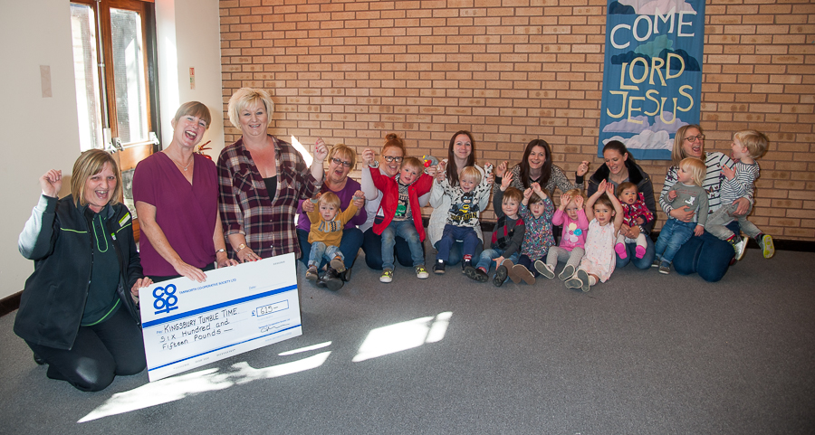 Emma Horsham, manager of Tamworth Co-op's Kingsbury convenience store, hands over cheque to Kingsbury Tumble Time chairperson Michelle Eldred and treasurer Sharon Wilkes in front of delighted children and parents.