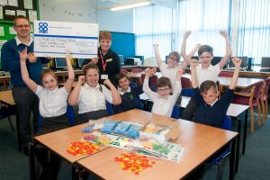 Sheila Villers, manager of Wood End convenience store, hands over cheque for £429 to Matt Hardman, assistant head teacher at Hurley Primary School, cheered on by some of delighted pupils.