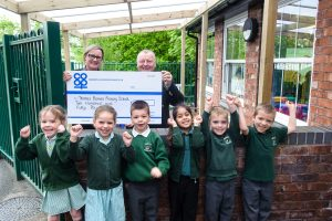 Ron Constable, general manager of Tamworth Co-op department store, presents cheque from Community Dividend Fund, to Emma Tibbitts, head of Thomas Barnes Primary School, cheered on by pupils.