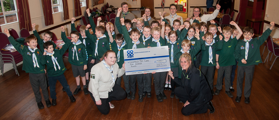 Nicky Gilbert, manager of Lichfield Co-op (centre) hands over Community Dividend Fund cheque to delighted Cubs