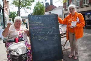 Margaret Baker enjoys a cup of coffee next to a blackboard containing people's bucket list wishes. Also pictured is Margaret Brown a community engagement officer with St Giles Hospice.