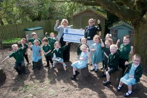 Tamworth Co-op department store floor controller Julie Plummer is pictured presenting the Community Dividend Fund cheque to the delight of pupils aged four and five.