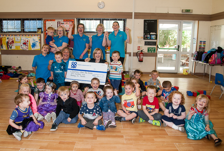 Dosthill Park Pre-School supervisor Lesley Williams receives Community Dividend Fund cheque from Vicky Freeman, manager of Dosthill Co-op. Also celebrating are pre-school practitioner Sandra Humphreys, deputy supervisor Chris Barron, pre-school practitioners Louise Ford, Jo Cooke and Sarah Griffin, along with children from pre-school.