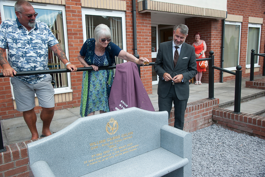 Gladys Galvin pours a tot of whisky over bench erected in memory of her late husband Bill, funeral director in Tamworth for many years, watched by his friend, Derek Barnbrook (left) and Glen Speak, deputy general manager of Tamworth Co-op funeral service.