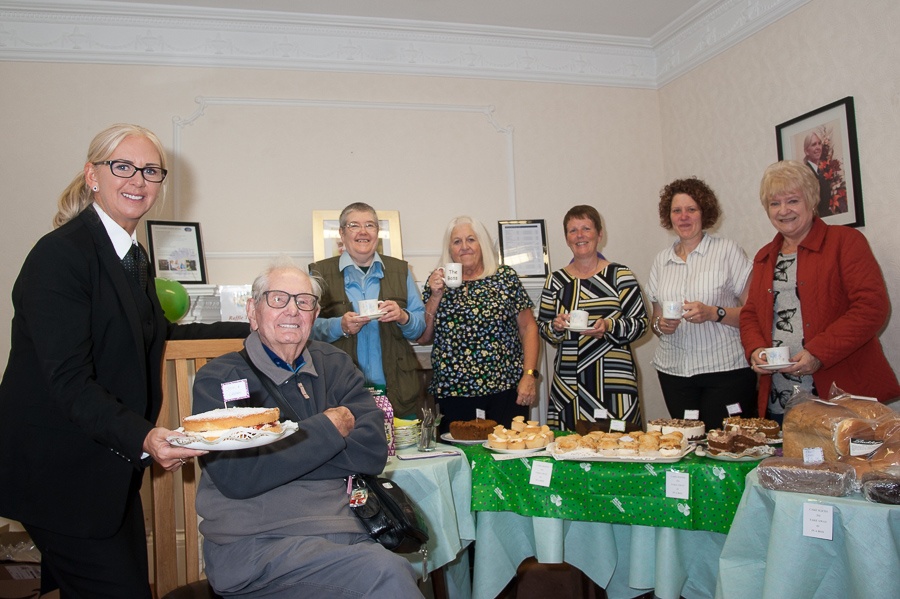 Woodville Co-op funeral director Lorraine Walker presents 99-year-old Joe Cave with cake as thank you for his generous donation. Looking on are Mr Cave's daughter Pauline, Woodville Co-op funeral arranger Sandra Wyatt, former Woodville Co-op funeral director Angela Bowyer, and visitors to coffee morning, Kerry Turner and Ethel Hull.