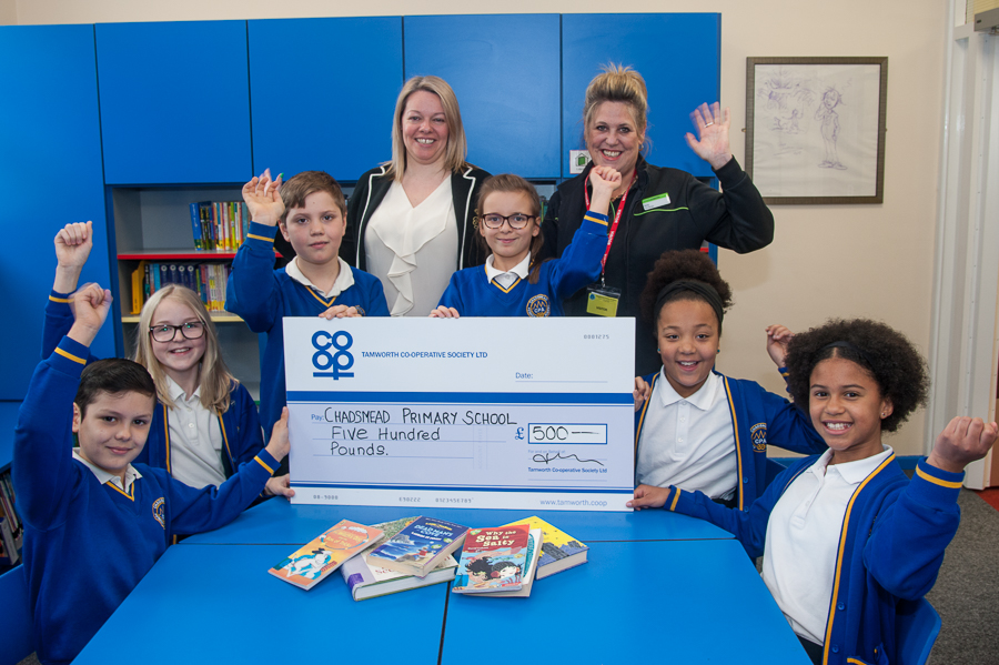 Chadsmead Primary Academy's designated young librarians celebrate as Nicky Gilbert (right), manager of Lichfield Co-op convenience store, presents cheque for £500 to head Gemma Grainger