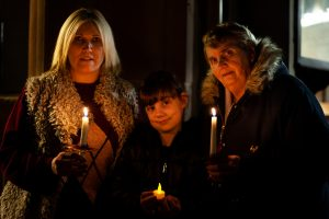 Mother, daughter and granddaughter holding lit candles at Tamworth Co-op Christmas Memorial Service