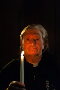 Vicar holding lit candle in memory of son