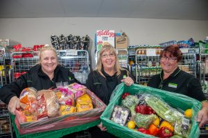 Tamworth Co-op supermarket staff with trays of surplus food to be sent to groups preparing meals for needy