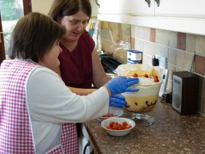 Resident of Polesworth Group Homes preparing food with staff member