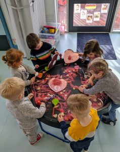 Young children involved in messy play a Coton in the Elms Pre-school