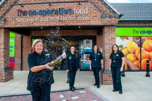 Dordon Co-op manager sprays champagne at opening watched by staff