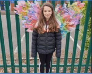 Schoolgirl wearing wings outside gate