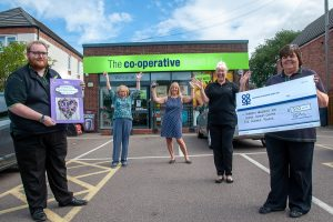 Wood End Co-op manager at presentation of Community Dividend Fund cheque with cheering representatives of Tamworth Wellbeing Cancer Support Centre