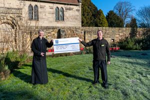 Vicar receives Community Dividend Fund cheque from Tamworth Co-op food store manager at Polesworth Abbey