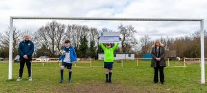Junior football player holding Community Dividend Fund cheque aloft with another player and manager and Tamworth Co-op manager in mouth of goal