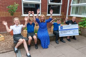 Whittington Co-op manager presents cheque to headteacher with pupils cheering