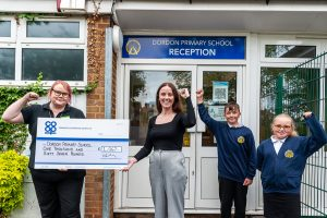 Dordon Co-op supervisor presents giant cheque to village school head watched by two pupils