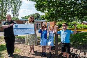 Kingsbury Co-op Community Dividend Fund presentation with store manager, headteacher and cheering pupils
